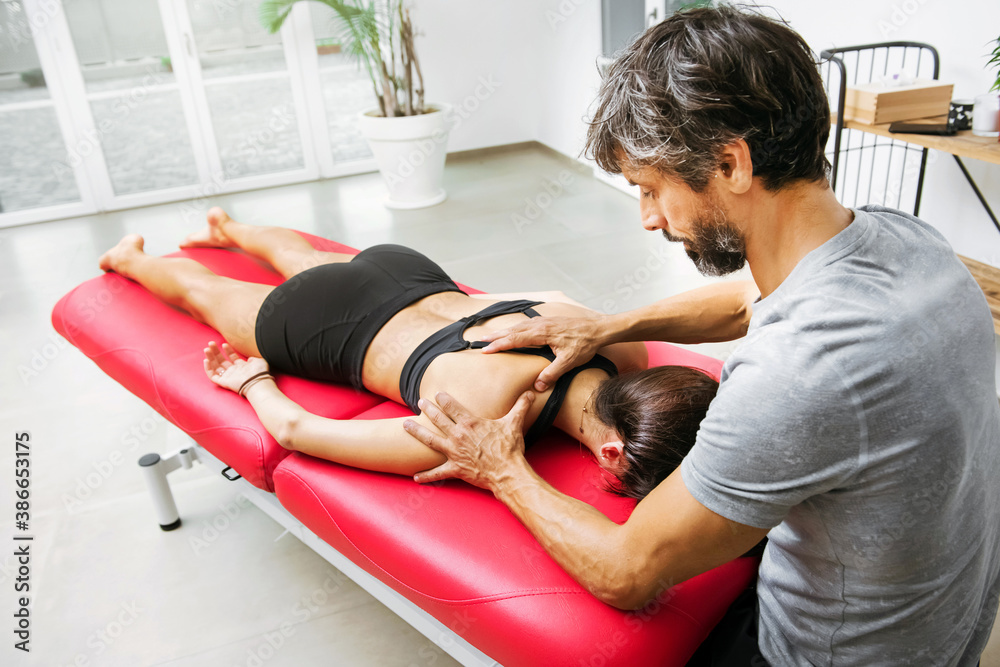 Fototapeta Osteopath doing a supraspinatus myofascial massage