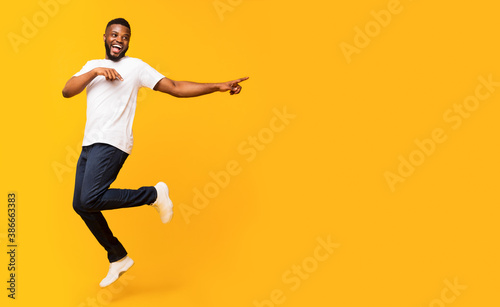 Fotografia Joyful black guy jumping up and pointing aside