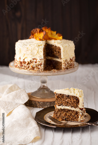 Naklejka premium Slice of homemade Hummingbird cake with whole cake in the background on a dark background, copy space