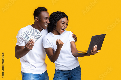 Emotional black couple celebrating win with laptop and cash Canvas-taulu