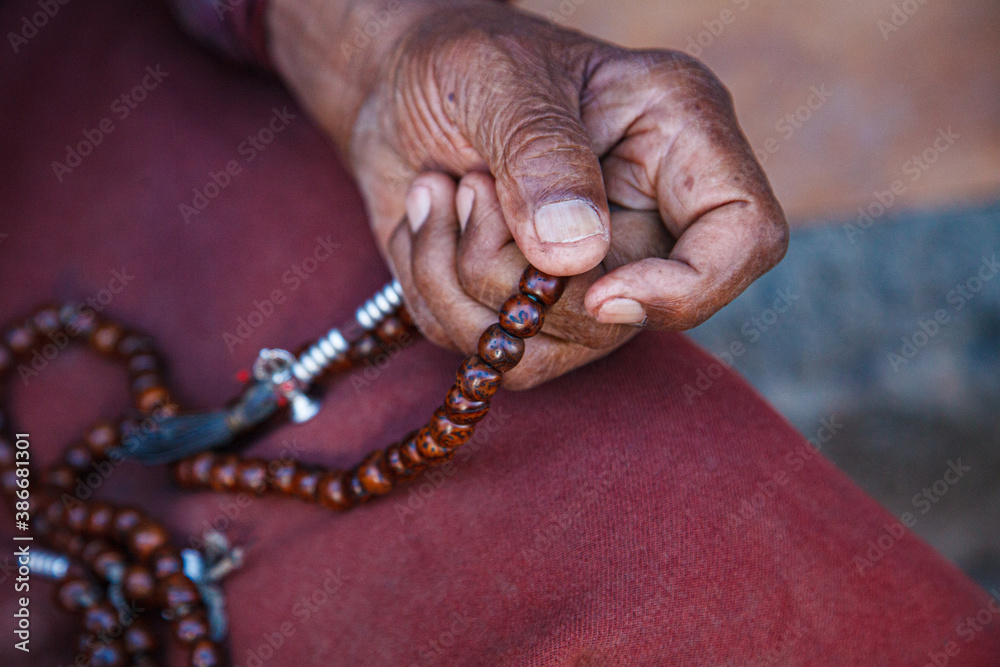 Fototapeta Old religious and believing Hindu 80 old in prayer to God with his fingers in a circle fingering beads or rosary and offering prayers.