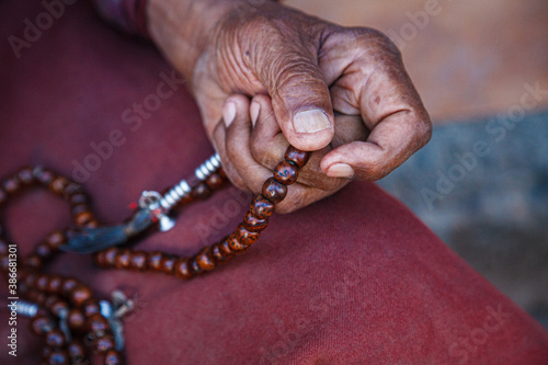 Fotografia, Obraz Old religious and believing Hindu 80 old in prayer to God with his fingers in a circle fingering beads or rosary and offering prayers