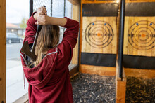Young Girl Throws An Axe At A Target In An Axe Throwing Range