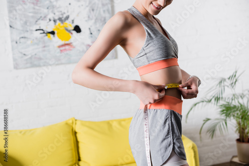 Obraz Cropped view of sportswoman measuring waist with tape at home - fototapety do salonu