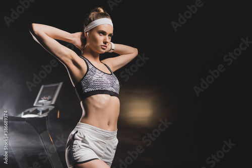 Obraz Sportswoman with hands behind head standing near treadmill in gym - fototapety do salonu