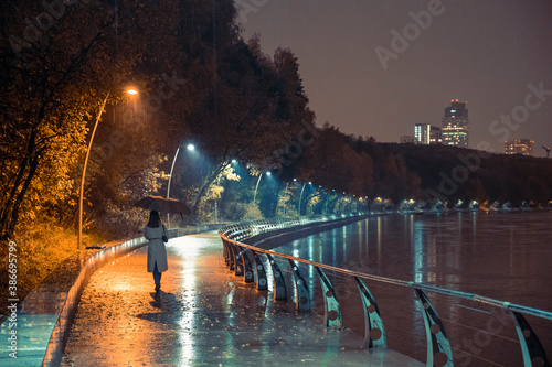 Girl with umbrella at night on the embankment in a heavy downpour Canvas Print