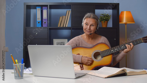 Canvas Print Senior woman in headset learning to play guitar online