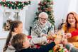 Leinwandbild Motiv Happy family toasting, sitting at festive table near fireside and christmas pine