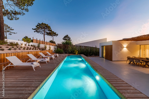 Obraz Modern house with garden swimming pool and wooden deck - fototapety do salonu