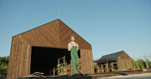 Young Man In Green Overalls Walking Out Of A Timber Shed With Scaffolding Visible Through The Open Door In A Low Angle Full Length View. Construction Of A New Private Houses Settlement.