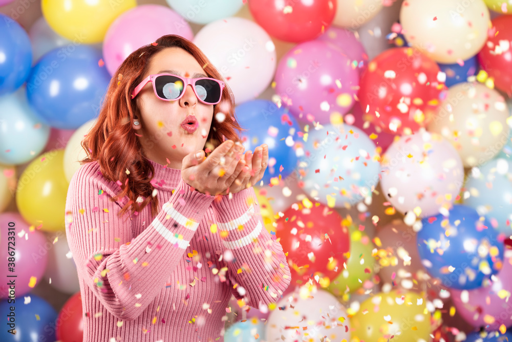 Fototapeta Happy young woman blowing confetti. Redheaded girl party alone on colorful balloons background