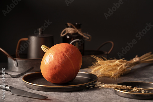 Vintage template with old metal tableware, ripe pumpkin and ear of wheat on black stone background for concept design Poster Mural XXL