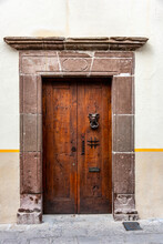 A Very Old Wooden Door With A Gargoyle Knocker