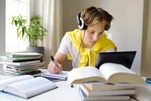 Teenager Boy Study At Home. Online Education And Distance Learning For Children. School Boy Doing His Homework Using Gadgets. Lectures And Lessons On The Internet For High School Students