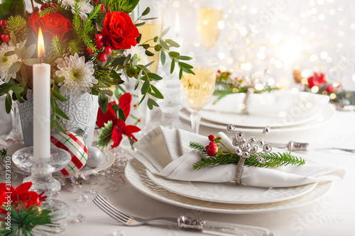 Festive table setting with winter flower arrangement on table decorated for holiday. Christmas or New Year dinner concept.