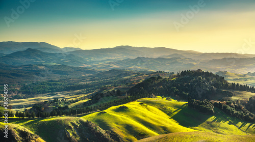 Naklejka premium Volterra winter panorama, rolling hills and green fields on sunset. Tuscany, Italy