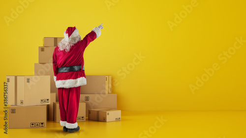 Obraz Santa Claus in front of cardboard boxes that indicates something in the wall - fototapety do salonu