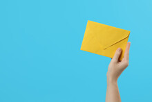 Woman Holding Yellow Paper Envelope On Light Blue Background, Closeup. Space For Text