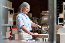 Older Mature Female Online Store Small Business Owner Worker Packing Package Scanning Postal Shipping Ecommerce Retail Order In Box Preparing Delivery Parcel On Desk In Warehouse. Dropshipping Service