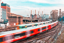 Trains On The Tracks And Power Station In London - Blurred Trains Leaving And Arriving Next A Busy Station - City Background With Buildings And Construction In Progress - Travel And Transport Concepts