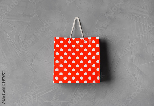 Obraz Paper shopping bag hanging on grey wall - fototapety do salonu