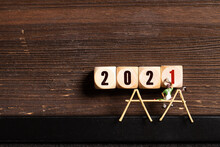 Little Painter Figures And Message 2021 On Wooden Cubes In Front Of Wooden Background