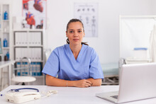 Portrait Of Pretty Medical Nurse Smiling At Camera In Hospital Office Wearing Blue Uniform. Healthcare Practitioner Sitting At Desk Using Computer In Modern Clinic Looking At Monitor, Medicine.
