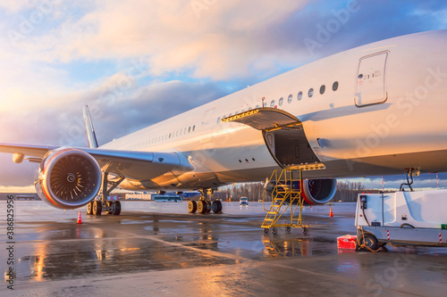 Airplane with open luggage compartment for passengers and wing and engine views Fotobehang