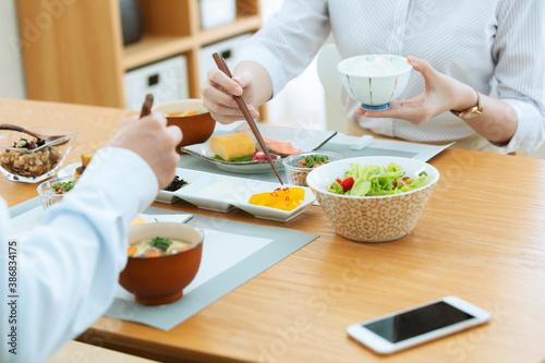 朝食を食べる夫婦 Fotobehang