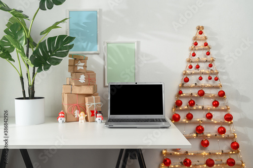 Obraz Christmas online shopping concept. Laptop and gifts on a white desk, original Christmas tree from branches in a home office. Morning sunshine. - fototapety do salonu