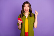 Portrait Of Delighted Girl Use Cellphone Enjoy Rejoice Social Network Lottery Raise Fists Scream Yes Wear Style Stylish Trendy Clothes Isolated Over Purple Color Background