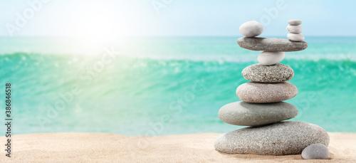 Pyramid of sea pebbles on a sunny sand beach Wallpaper Mural