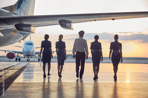 Obraz Back view image of unrecognizable people going to the aircraft in the outdoors - fototapety do salonu