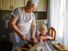 Elderly Father In Apron And Blond Son Preparing Breakfast In Kitchen
