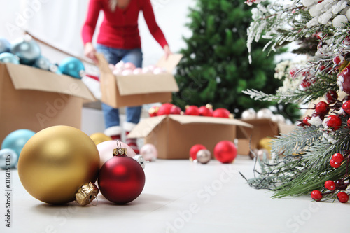 Foto Woman prepare christmas tree with cardboard boxes full of christmas balls and de