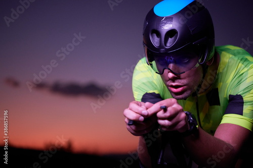 triathlon athlete riding bike fast at night Canvas