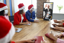 Group Of Business Men And Women In Protective Face Masks And Santa Hats Are Sitting At Table And Looking At Computer With Director On Screen In Office. Conducting Online Seminars During The Covid19