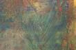Odbity liść w farbie w namalowanym, wielokolorowym, abstrakcyjnym tle, faktura.