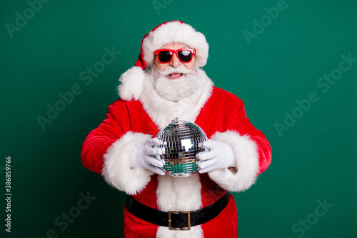Obraz Portrait of his he nice attractive handsome cheerful Santa grandfather mc pj father having fun holding in hands silver glossy ball newyear celebratory good mood isolated over green color background - fototapety do salonu