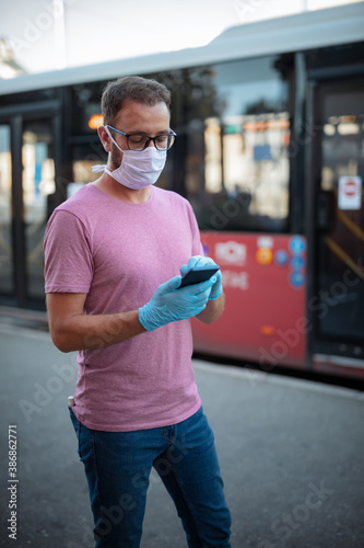 Obraz Man with medical protective mask and gloves waiting for a public transportation on a bus-stop and using smartphone. - fototapety do salonu