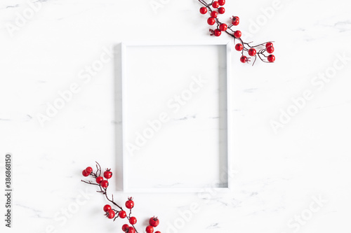 Christmas composition. Red berries, photo frame on marble background. Christmas, winter, new year concept. Flat lay, top view - 386868150