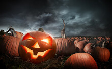 A Carved Glowing Halloween Pumpkin In A Field At Night. Photo Composite.