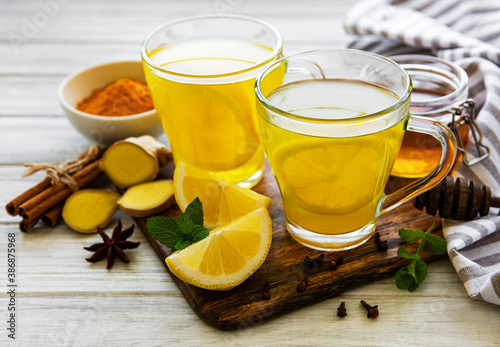 Obraz Energy tonic drink with turmeric, ginger, lemon and honey on a white wooden background - fototapety do salonu