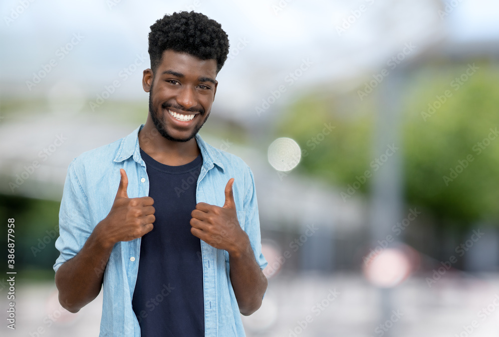 Fototapeta Cheering young adult man from Africa with beard and casual clothes