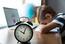 Boy Not In Focus Felt Asleep During Distance Online Math Lesson . Clock Shows Time. Too Tired And Exhausted On E-learning.  Home Distant Learning Concept.
