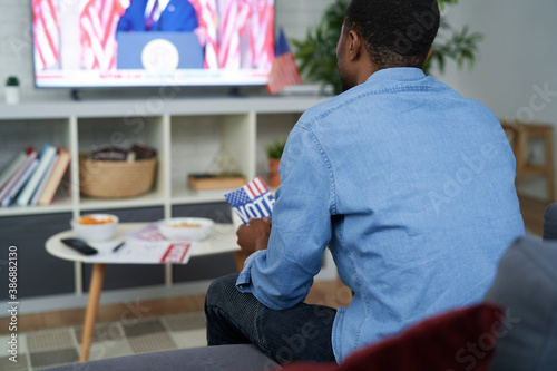 Rear view of  affectionate man watching USA election on TV Wallpaper Mural