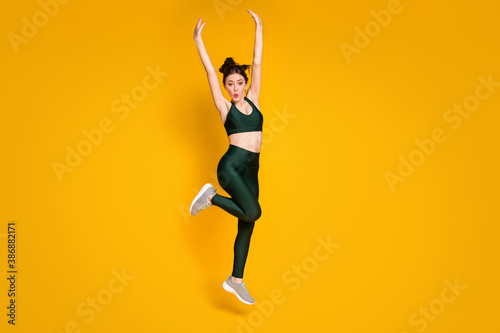 Fototapeta Full size photo of sportive lady jump high up active person raise arms wear sports suit sneakers isolated yellow color background obraz