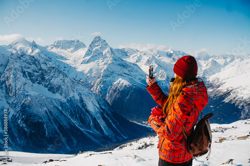 A woman with a backpack takes pictures in the mountains in winter. Tourist on excursions in the mountains.