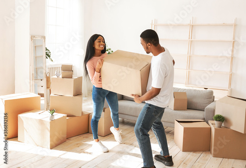 Photo Happy African American woman and her husband carrying cardboard box with their p