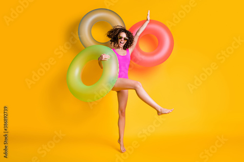 Photo portrait of excited girl standing on one leg wearing pink swim wear holding green red blue inflatable ring isolated on vivid yellow colored background
